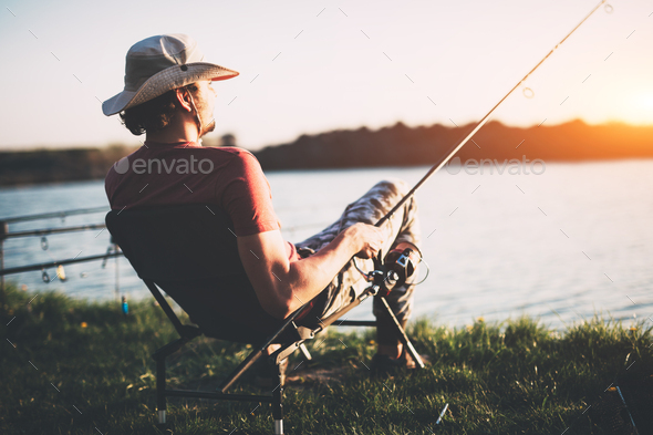 Young man fishing at pond and enjoying hobby - Stock Photo - Images