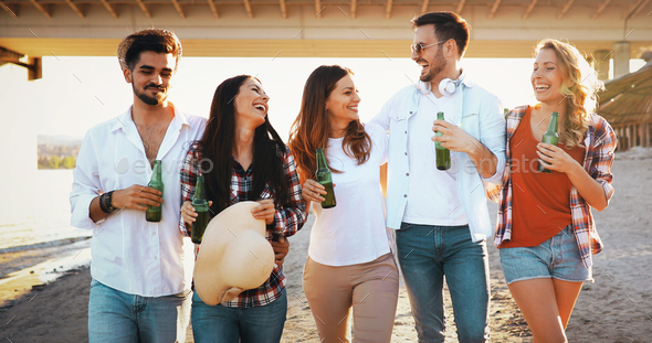 Group of happy friends partying on beach - Stock Photo - Images