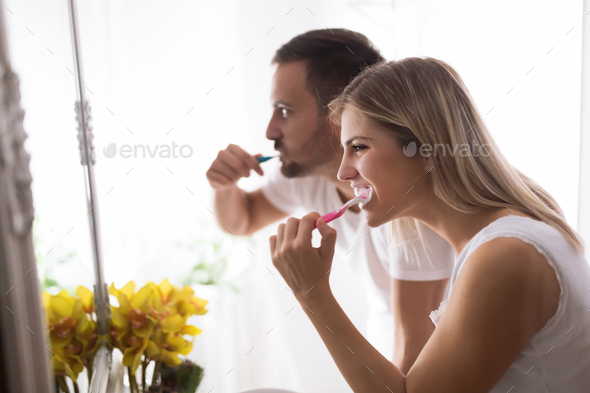 Attractive couple washing teeth in morning together - Stock Photo - Images