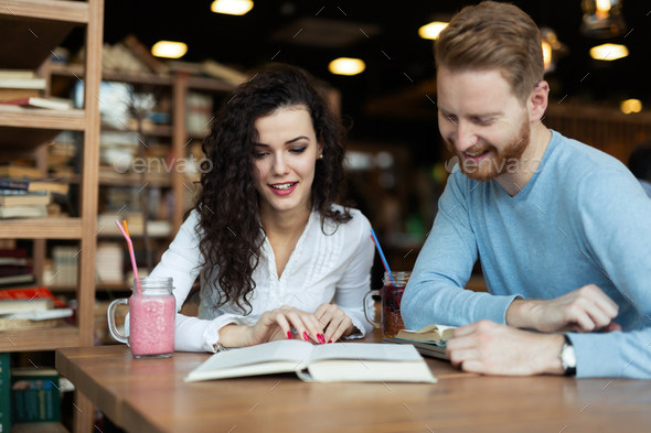 Young students spending time in coffee shop reading books - Stock Photo - Images