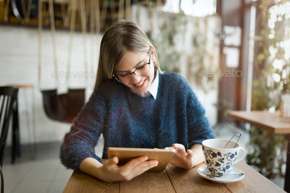 Happy young woman drinking coffee and using tablet - Stock Photo - Images