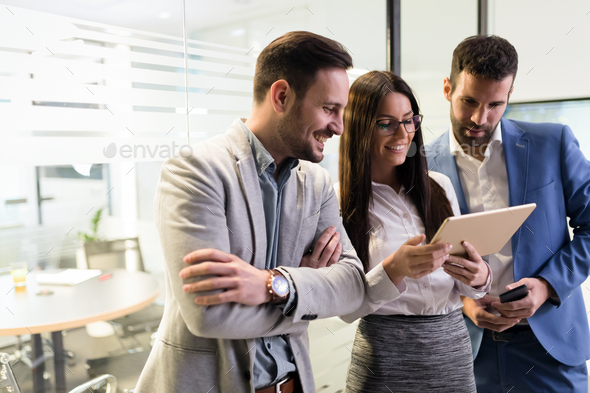 Businessmen and businesswoman using tablet in office - Stock Photo - Images