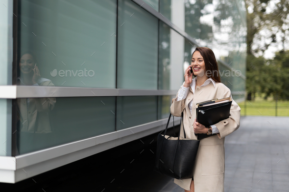 Attractive and beautiful businesswoman walking and talking - Stock Photo - Images
