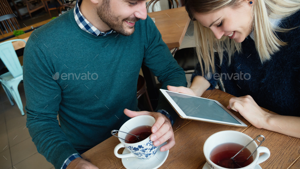 Young attractive man and beautiful woman on date looking on tablet - Stock Photo - Images