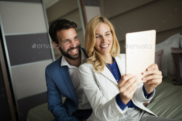 Businessman and businesswoman sitting on bed and using tablet - Stock Photo - Images