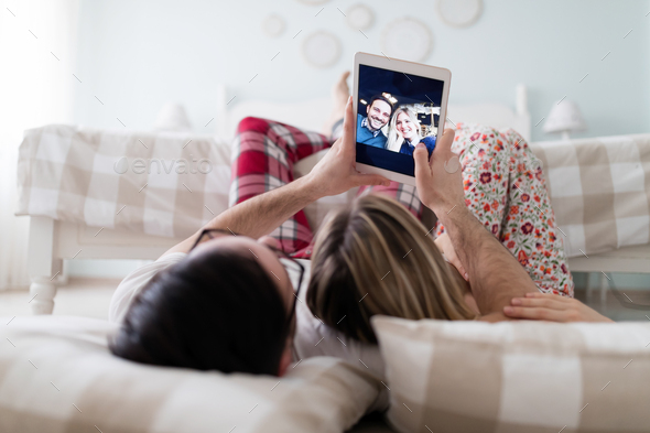 Young attractive couple using digital tablet in bedroom - Stock Photo - Images