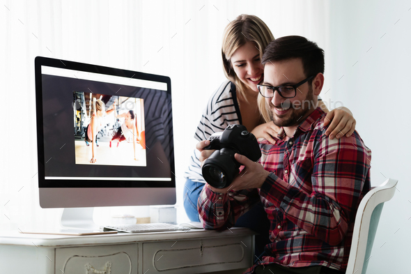 Young couple of designers working on computer - Stock Photo - Images