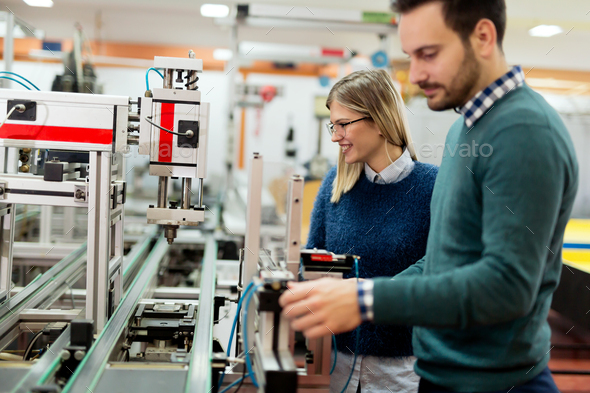 Two young handsome engineers working on electronics components - Stock Photo - Images
