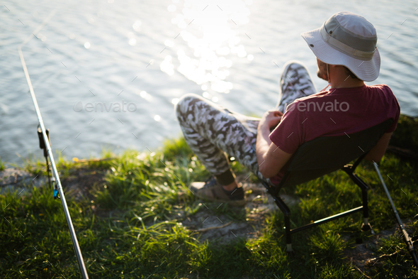 Fishing as recreation and sports displayed by fisherman at lake - Stock Photo - Images