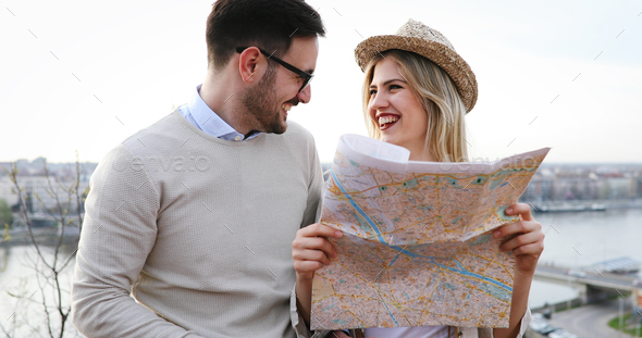 Happy tourists sightseeing city with map - Stock Photo - Images