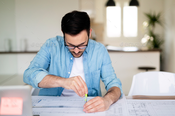 Portrait of a young businessman working on blueprints at the office - Stock Photo - Images