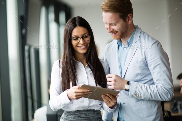 Portrait of attractive business partners using tablet - Stock Photo - Images