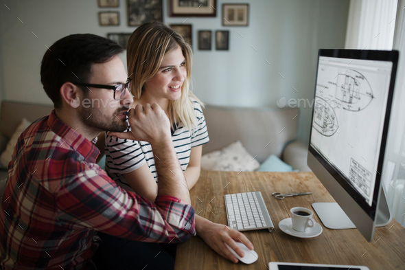 Beautiful woman and attractive man doing design work - Stock Photo - Images