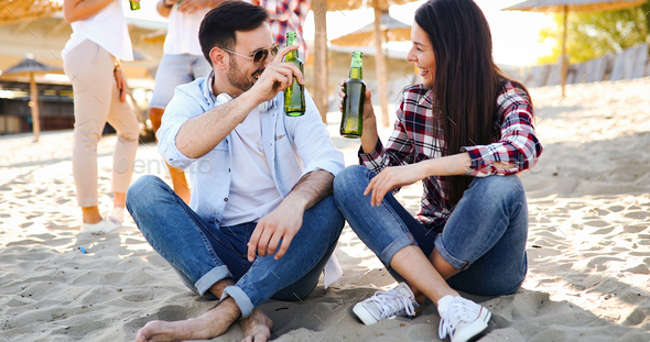 Group of young friends laughing and drinking beer - Stock Photo - Images