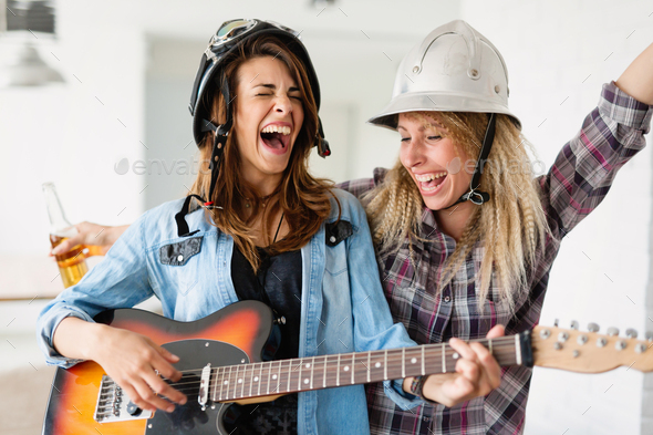 Cheerful friends having party together and playing instruments - Stock Photo - Images