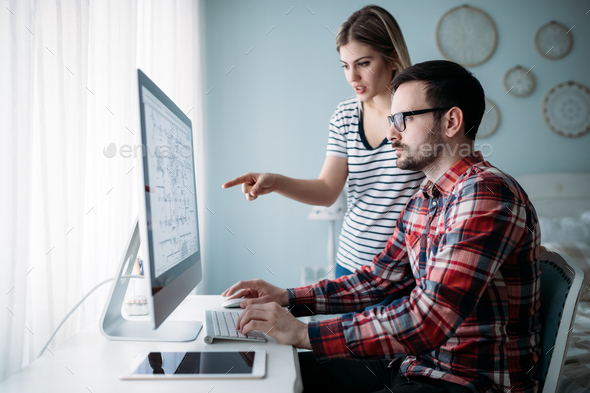 Young attractive designers working on project together - Stock Photo - Images