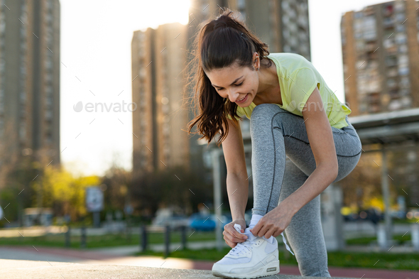 Young woman tying sports shoe - Stock Photo - Images