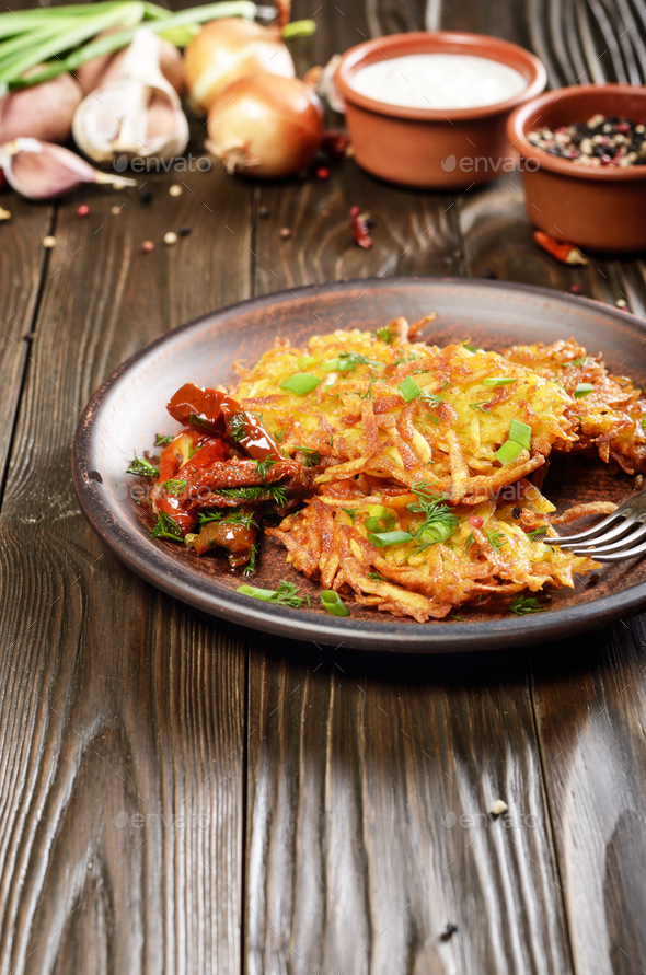 Homemade tasty potato pancakes in clay dish with sun-dried tomat - Stock Photo - Images