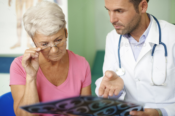Doctor with his senior patient analyzing medical test - Stock Photo - Images