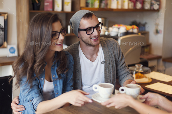 Fashion couple receiving cup of coffee from waitress - Stock Photo - Images