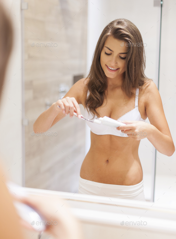Morning routine by brushing teeth in bathroom - Stock Photo - Images