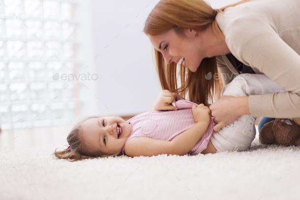 Loving mother tickling her little girl on carpet at home - Stock Photo - Images
