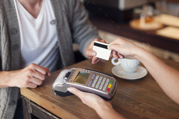 Close up of customer paying by credit card - Stock Photo - Images
