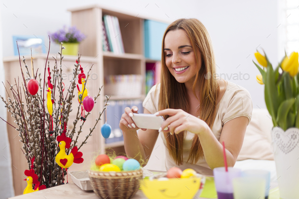 Happy woman taking photo by mobile phone in easter holiday - Stock Photo - Images