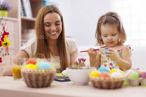 Focus little girl painting easter eggs with her mother - Stock Photo - Images