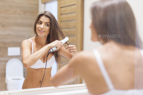 Smiling woman straightening hair in front of mirror - Stock Photo - Images