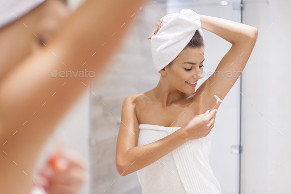 Woman shaving armpit in bathroom - Stock Photo - Images