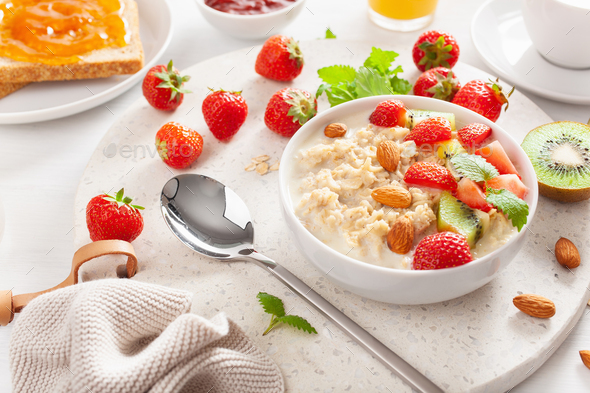 healthy breakfast with oatmeal porridge, strawberry, nuts, toast - Stock Photo - Images