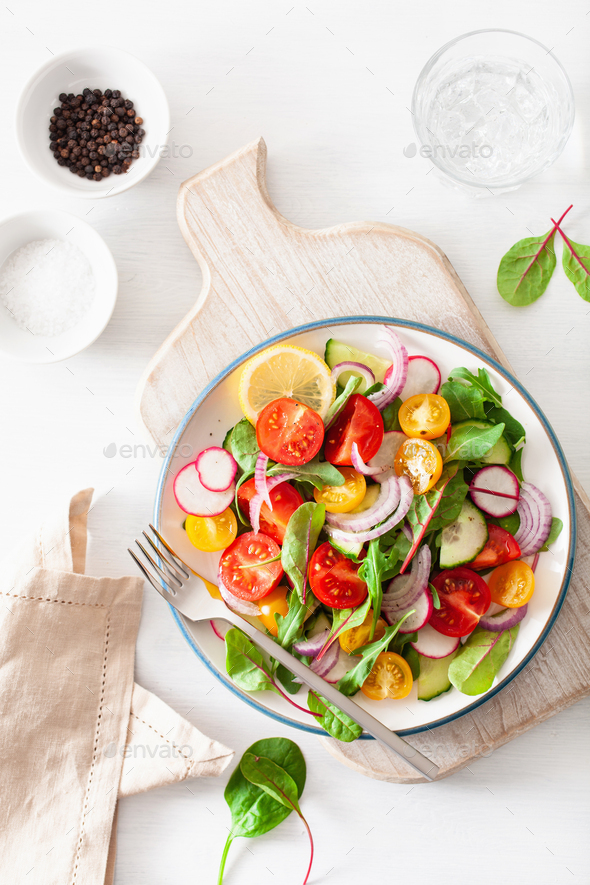 healthy colorful vegan tomato salad with cucumber, radish, onion - Stock Photo - Images