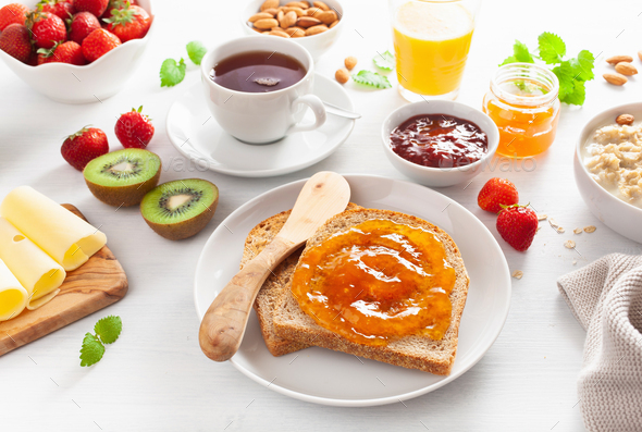 healthy breakfast with toast, strawberry, nuts, jam and tea - Stock Photo - Images