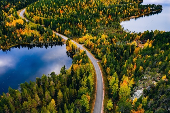 Aerial view of road and colorful autumn  forest with mountains and blue lakes in Finland. - Stock Photo - Images