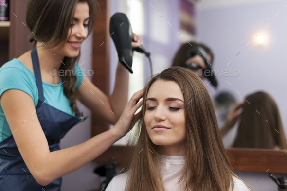 Hair stylist drying woman's hair - Stock Photo - Images