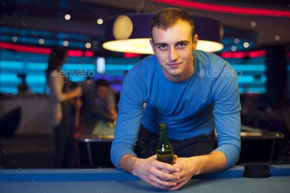 Portrait of handsome man in billiard club - Stock Photo - Images