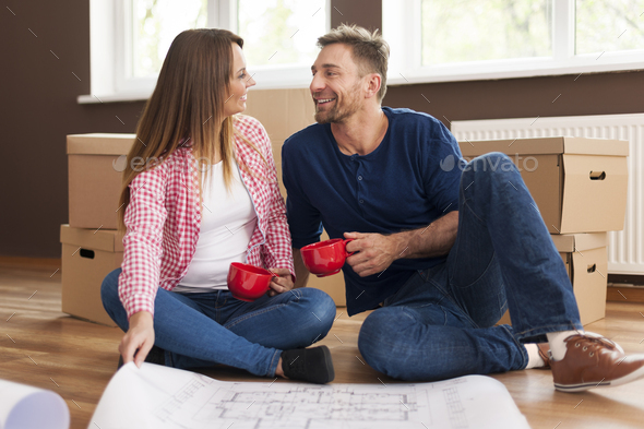 Happy couple relaxing in new home - Stock Photo - Images