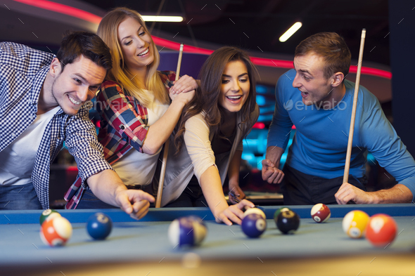Group of young friends playing billiard - Stock Photo - Images
