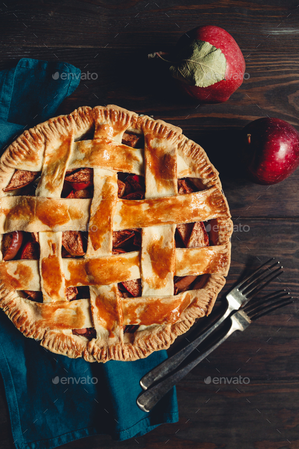 Top view on an apple pie on a wooden table. Rustic moody food photography. - Stock Photo - Images