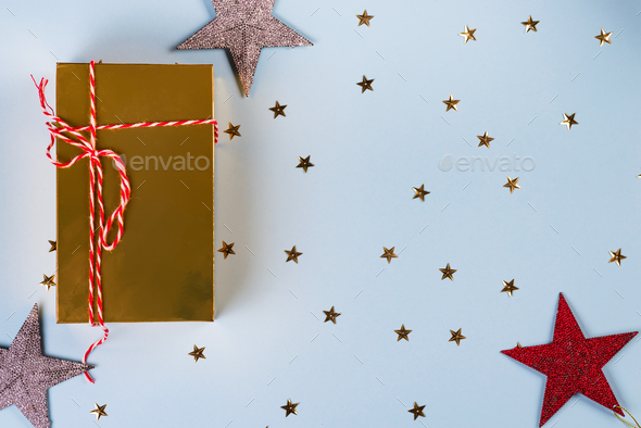 Christmas pattern made of golden, silver, red stars with golden gift box on blue background. Winter - Stock Photo - Images