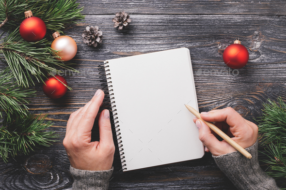 Woman's Hand Writting in Notebook and Christmas Decorations. - Stock Photo - Images