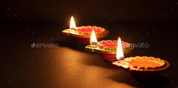 Happy Diwali. Diya colorful oil lamps, dark background - Stock Photo - Images