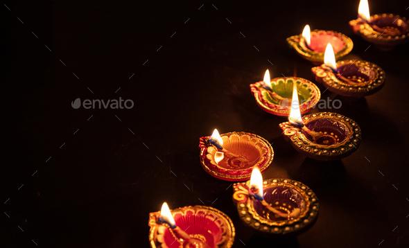 Diwali, Hindu festival of lights celebration. Diya oil lamps against dark background, - Stock Photo - Images