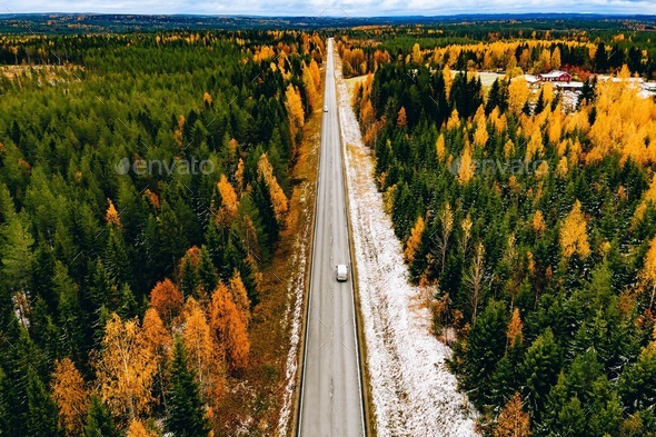 Aerial view of first snow autumn color forest and a road with car in Finland. - Stock Photo - Images