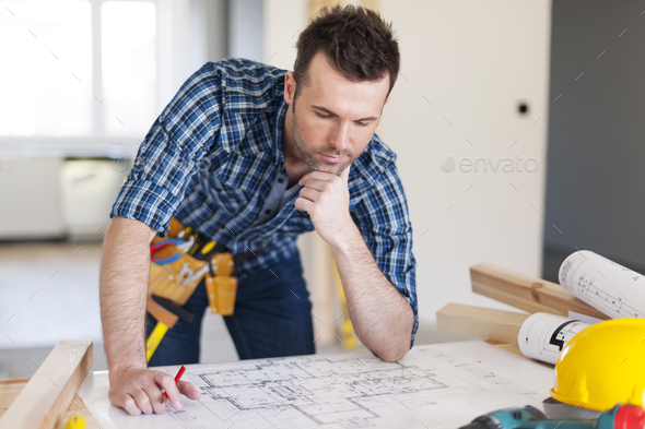 Building contractor bending over home plans - Stock Photo - Images