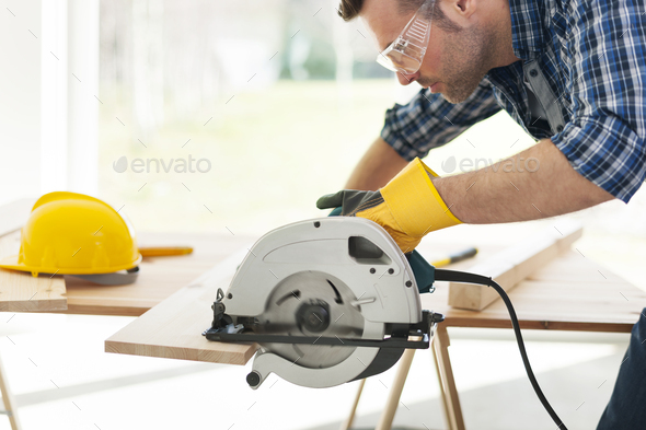 Male carpenter sawing wooden boards - Stock Photo - Images