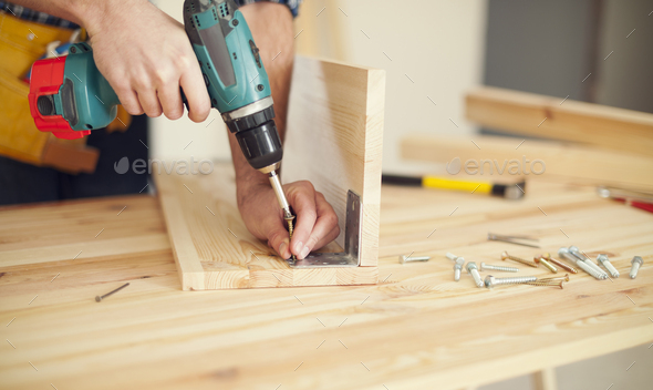 Close up of carpenter working with drill - Stock Photo - Images