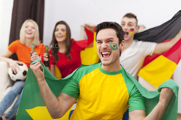 Excited brazilian man with her friends cheering football match - Stock Photo - Images