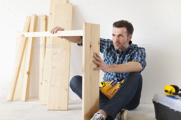 Handsome carpenter working on new furniture - Stock Photo - Images